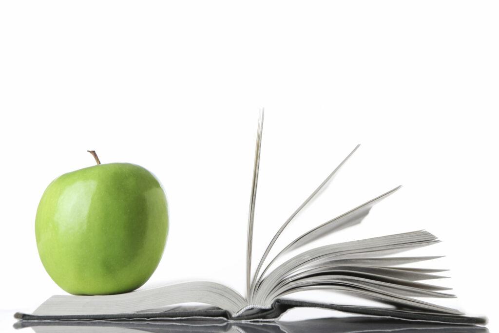 En öppnad bok med ett äpple
